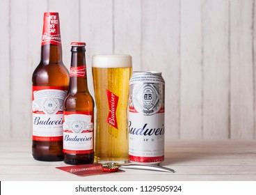 LONDON, UK - APRIL 27, 2018: Glass bottles and aluminium cans of Budweiser Beer on wooden background with bottle opener. An American lager first introduced in 1876.