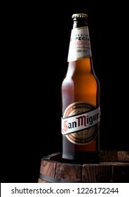 LONDON, UK - APRIL 27, 2018: Bottle of San Miguel lager beer on top of old wooden barrel. The San Miguel brand of beer is the leading brand of the San Miguel Brewery Inc.
