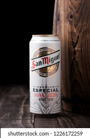 LONDON, UK - APRIL 27, 2018: Aluminium can of San Miguel lager beer next to wooden barrel. The San Miguel brand of beer is the leading brand of the San Miguel Brewery Inc.