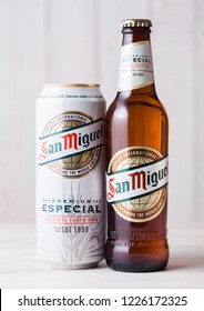 LONDON, UK - APRIL 27, 2018: Bottle and aluminium can of San Miguel lager beer on wooden background. The San Miguel brand of beer is the leading brand of the San Miguel Brewery Inc