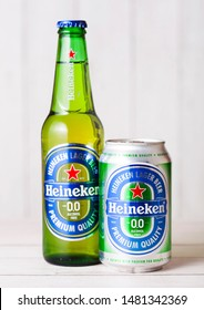 LONDON, UK - APRIL 27, 2018: Bottle and aluminium can of Heineken Non Alcoholic Lager Beer on wooden background. Heineken is the flagship product of Heineken International