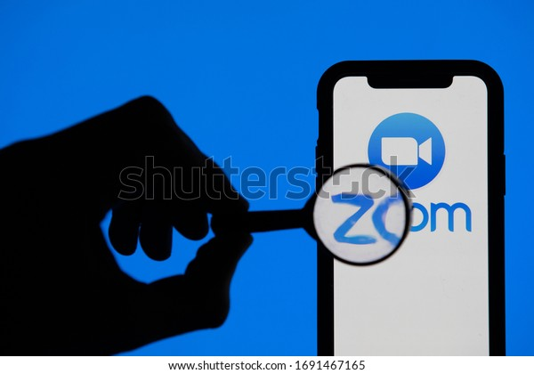 LONDON, UK - April 2nd 2020: Magnifying glass looking at Zoom video conference app on a smartphone