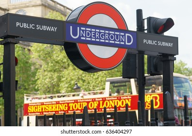 LONDON, UK - April 30, 2014: Underground sign and the bus of sightseeing tour of London in background.