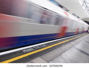 London, UK - April 4: Blurred fast moving underground train entering station. Mind The Gap warning in foreground.
