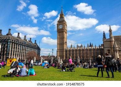 London, UK, April 6, 2012 : Parliament Square with tourists showing Big Ben of the Houses of Parliament and Portcullis House which is a popular tourism travel destination landmark, stock photo image