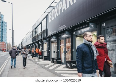 London, UK - April 6, 2019: People walking past the shops at BOXPARK Shoreditch, London, shipping container pop-up mall for independent and fashion and lifestyle stores and cafes.