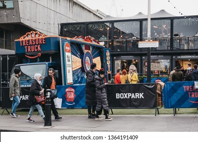 London, UK - April 6, 2019: People walking past Amazon truck parked at BOXPARK Shoreditch, shipping container pop-up mall for independent and fashion and lifestyle stores and cafes.