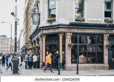 London, UK - April 6, 2019: People standing and drinking outside The Ten Bells pub in Shoreditch, East London, pub famous for its supposed association with two victims of Jack the Ripper.