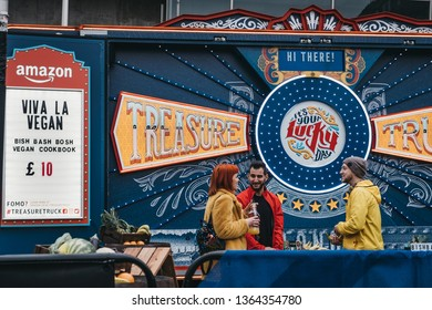 London, UK - April 6, 2019: People talking in front of Amazon treasure truck parked at BOXPARK Shoreditch, shipping container pop-up mall for independent and fashion and lifestyle stores and cafes.