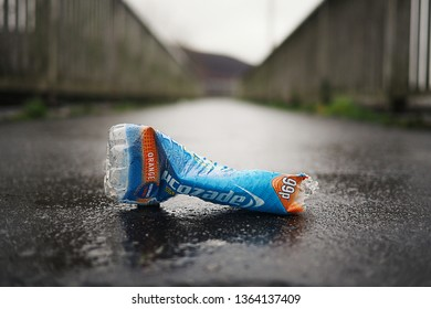 London, UK / April 9th 2019 : Recently discarded plastic bottle on wet concrete urban footpath, an example of how society discards non-recyclable waste.