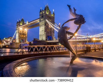 """LONDON, UK - AUG 1: Girl With A Dolphin Fountain"""" by English artist David Wynne in front of the tower bridge on August 1, 2017 in London, UK. This spot is a popular place for selfies in London."""