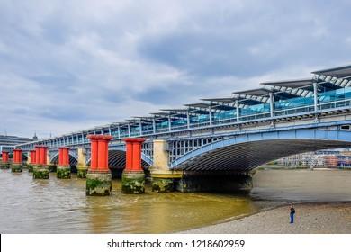 London, U.K, Aug 2018, man standing on the Thames riverbank at low tide by the Blackfriars Railway Bridge, England