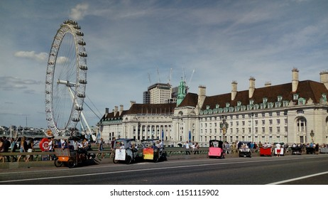 LONDON/ UK- AUG 8 2018: People and families enjoying a summers day, and rickshaw rides, on Westminster bridge, with county hall and the London eye in the background.