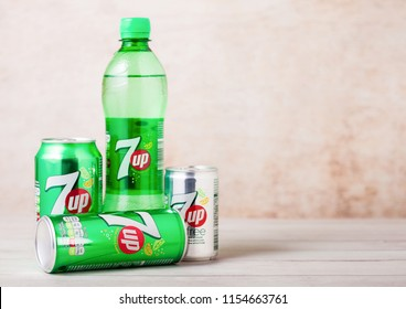 LONDON, UK - AUGUST 03, 2018: Plastic bottle and aluminium cans of 7UP citrus soda drink on wood.