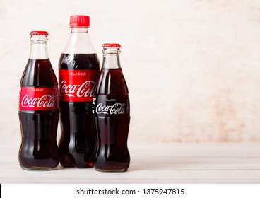 LONDON, UK - AUGUST 03, 2018: Plastic and glass bottle of Original Coca Cola soft drink on wood. Most popular drink in the world.