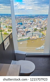 London, UK - August 1, 2015: View through the floor-to-ceiling window of a public restroom in a skyscraper to the Thames and London in the UK.