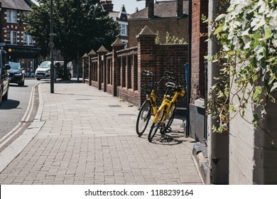 London, UK - August 1, 2018: Yellow Ofo bikes on a street in London. Ofo is a dockless bike-sharing company that deployed over 10 million bicycles in 250 cities and 20 countries.