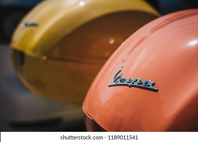 London, UK - August 1, 2018: Close up of two colourful Vespa motorbikes parked by a house in Barnes, London. Vespa is a famous Italian brand of scooter manufactured by Piaggio.