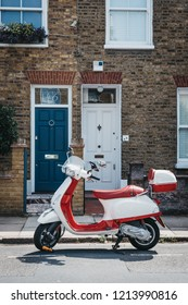 London, UK - August 1, 2018: Red and white Vespa motorbike parked by a house in Barnes, London. Vespa is a famous Italian brand of scooter manufactured by Piaggio.