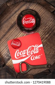 LONDON, UK - AUGUST 10, 2018: Coaster of Original Coca Cola soft drink with bottle top and opener and bottle on top of wood barrel.