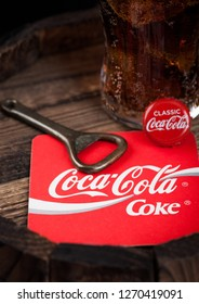 LONDON, UK - AUGUST 10, 2018: Coaster of Original Coca Cola soft drink with bottle top and opener and original glass on top of wood barrel.