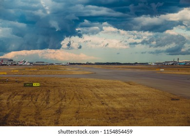 LONDON, UK - August 10th, 2018: view of Heathrow airport with stormy skies and airplanes at their stands