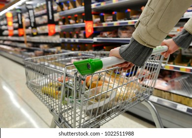 London, UK - August 18, 2014: A shopping pushes a trolley along an aisle in an ASDA supermarket. American company Walmart owns Asda, which with 568 stores is UK's largest retail chain after Tesco.