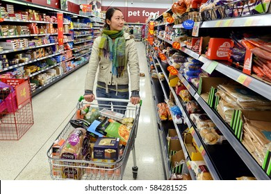 London, UK - August 18, 2014: A shopper browses an aisle at an Asda supermarket. Walmart owned Asda is the UK's 2nd largest retail chain after Tesco with 568 stores and an income of £638 mln in 2013.