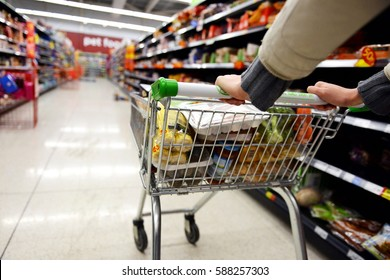 London, UK - August 18, 2014: A shopper pushes a trolley along an aisle in an Asda supermarket. American company Walmart owns Asda, which is UK's largest retail chain after Tesco with 568 stores.