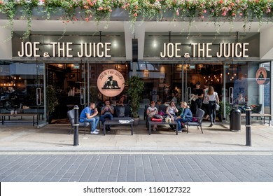 LONDON, UK - AUGUST 19, 2018: Joe & The Juice coffee shop & juice bar in Soho, Central London. People sitting outside drinking coffee and juice. Warn summer day in London.