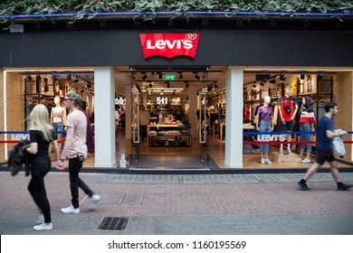 LONDON, UK - AUGUST 19, 2018: People walking in front of Levi's store in Carnaby Street. Levi Strauss & Co is a privately held American clothing company known worldwide for its   brand of denim jeans.