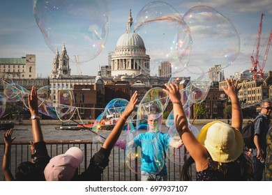 London (UK) - August 2017. Young kids having fun with soap bubbles made by a street performer on the South Bank of the Thames, with St. Paul's Cathedral in the background.