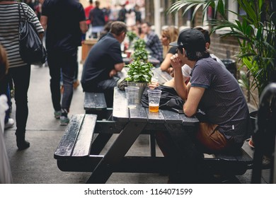 London, UK - August, 2018. Young people drinking beer in a pub in Brick Lane, Shoreditch.