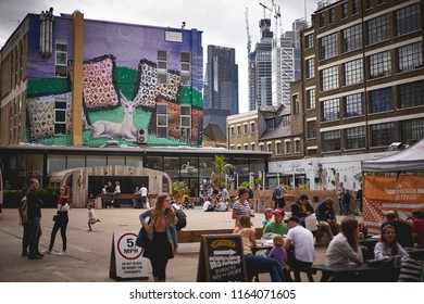 London, UK - August, 2018. Young people drinking outdoor in Brick Lane, near Shoreditch.