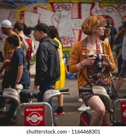 London, UK - August, 2018. A young tourist taking photos in a crowded Brick Lane in Shoreditch.