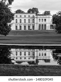London UK, August 2019. Newly renovated mansion at Gunnersbury Park on the Gunnersbury Estate, once owned by the Rothschild family, reflected in a lake in the park. Photographed in monochrome.