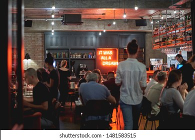 London, UK - August, 2019. Young people having drinks in a bar in Soho, central London.