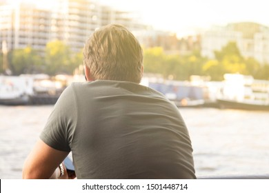 London, U.K. August 22, 2019 - Young man from the back, businessman standing at the Thames riverside in the city of London admiring the view. Vertical iimage.