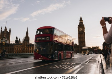 LONDON, UK - AUGUST 27, 2015: Tourists walking across westminster bridge, and a London bus driving past