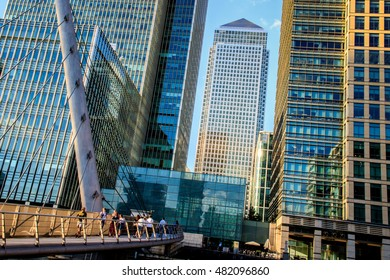 London, UK - August 29, 2016 - People walking on the South Quay footbridge in Canary Wharf with One Canada Square in the background