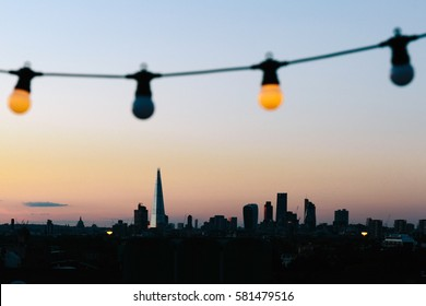 LONDON, UK - AUGUST 30, 2016: View of London skyline silhouette from an outdoor cinema party at Bussey Building Rooftop, Peckham, during sunset.