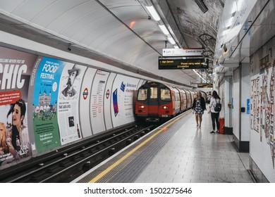 London, UK - August 31, 2019: People at Tottenham Court Road London Underground station platform, motion blur, selective focus. London Underground is the oldest underground railway in the world.