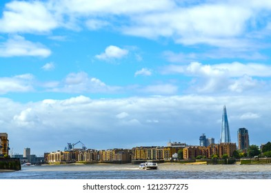 London, UK - August 4, 2015: View to the shore development of the Thames at ebb tide and the skyline of London, UK