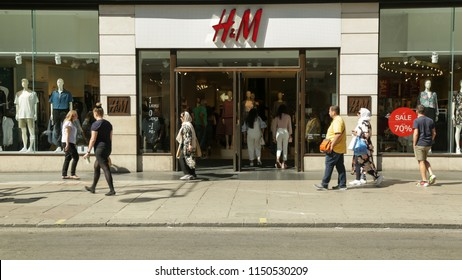 LONDON, UK - August 5th 2018: H&M clothing store on Oxford Street in central London. Summer sale season, view of exterior with shoppers walking across the Oxford Street.