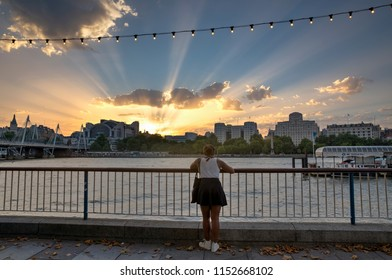 LONDON, UK - AUGUST 6, 2018 :  A young woman on the South Bank of the River Thames looks at the Crepuscular rays as the sun sets behind Charing Cross Station.