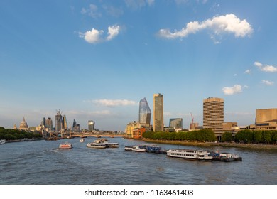 LONDON, UK - AUGUST 6, 2018 :  Boats on the River Thames by Waterloo Bridge with the Southbank centre, Blackfriars Bridge, St Paul's and city skyscrapers in the background.