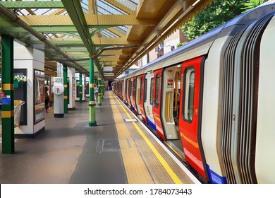 London, UK. August 6, 2018. London underground station platform almost empty, a person in the distance is boarding the train with all the doors open. The station is on an open-air line.