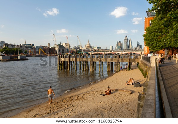 LONDON, UK - AUGUST 6, 2018 : People on the small beach at the shore of the Thames by Gabriel's Wharf on the South Bank of England's capital city with St Paul's and city skyscrapers in the background