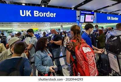 London, UK- August 6, 2021: Air travelers with face mask queuing at UK border control in Heathrow Airport, London.