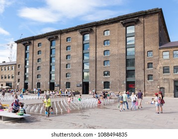 LONDON, UK - AUGUST 9, 2015: People playing in the water fountain outside the redeveloped Granary Building in King's Cross.